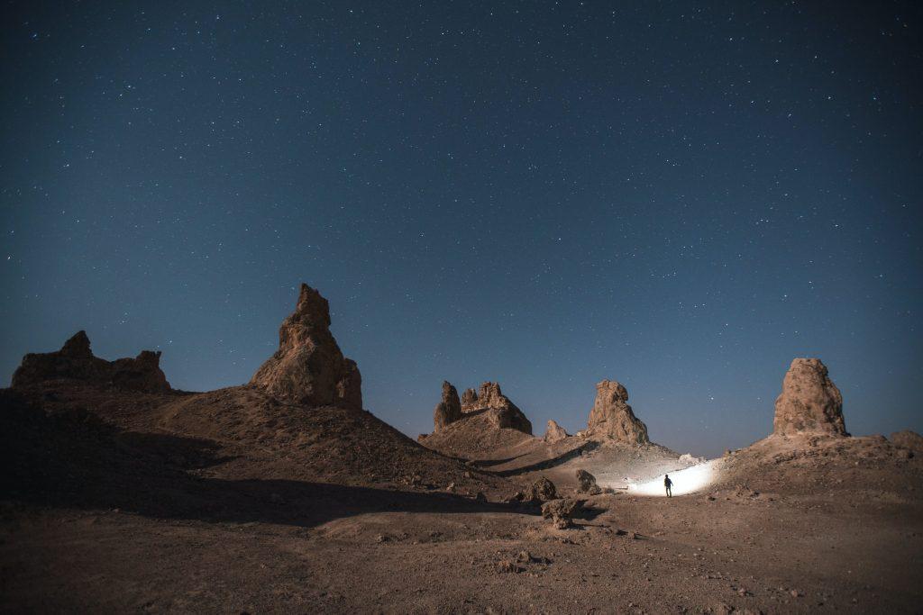 Un hombre caminando a través del desierto con una linterna