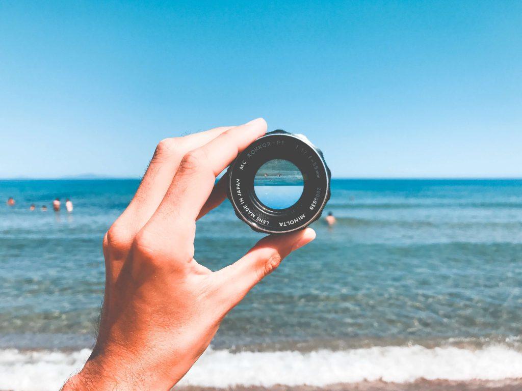 Imagen de alguien con un objetivo de una cámara en la playa
