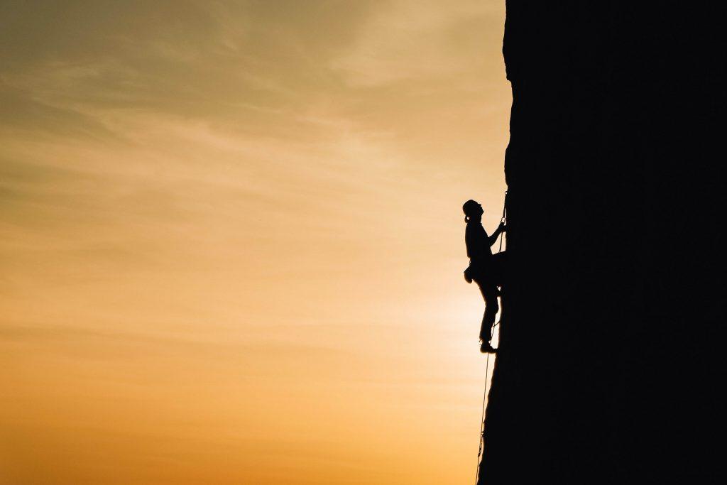 Una persona escalando una pared vertical de una montaña