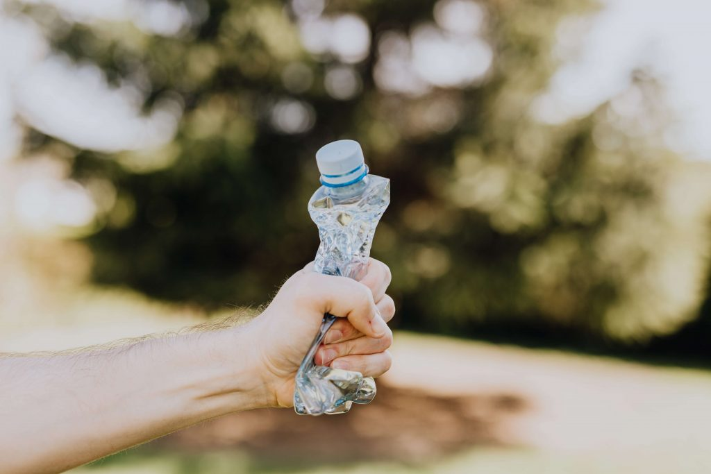 Imagen de una persona comprimiendo una botella con su mano