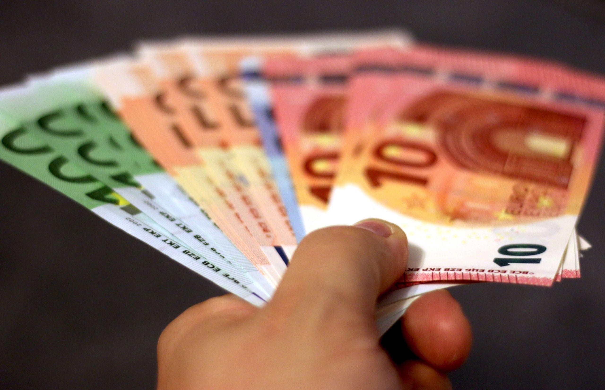 Una mano con un fajo de billetes de euros