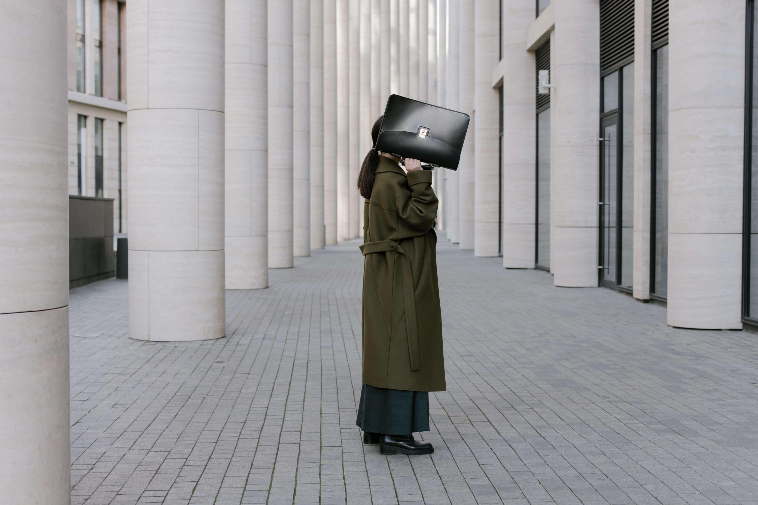 Mujer esconde su cara tras un maletín